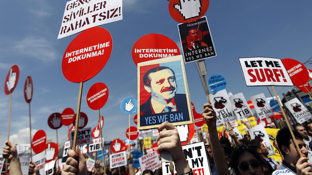 Demonstrators hold placards with some featuring a picture of Turkey's PM Erdogan during a protest against internet censorship in Istanbul