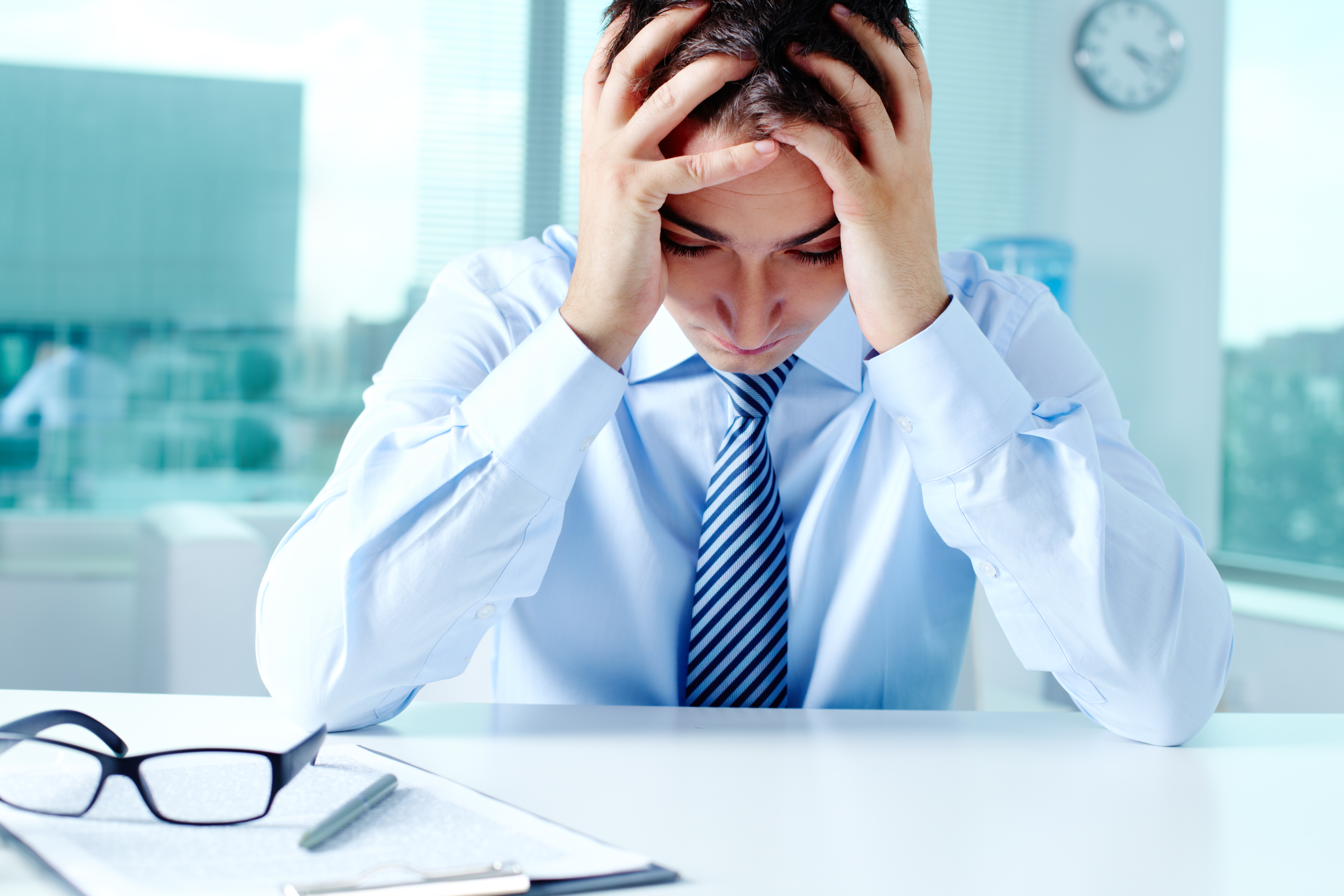 Stressed businessman sitting at workplace and touching his head
